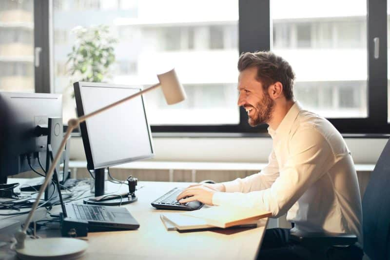 man in office behind at desk smiling