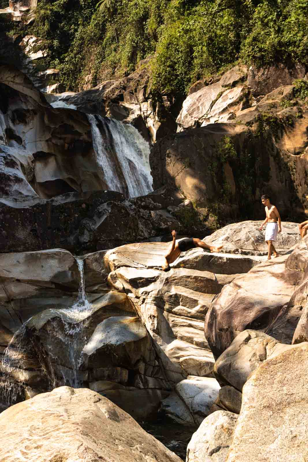 Locals jumping off the rocks at Tarapoto Falls in Jardin, Colombia.