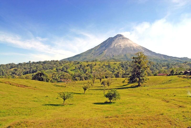 Volcano with grassy plains with trees in foreground in Costa Rica