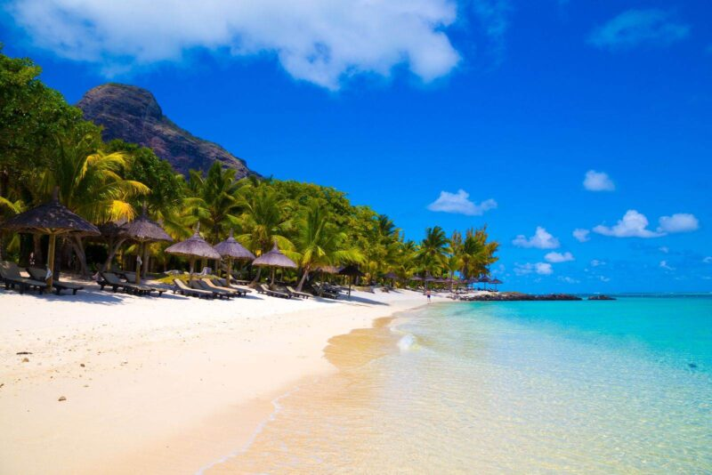 Tropical beach with beach huts lining it in Mauritius