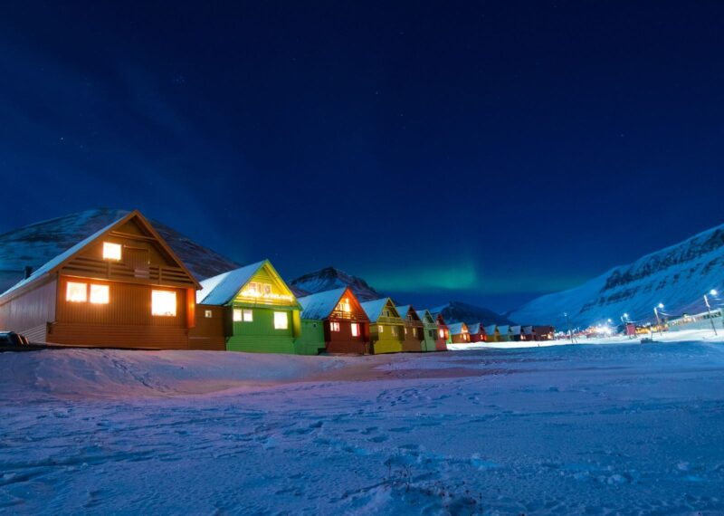 Huts lit up at night in the snow in Svalbard in Norway