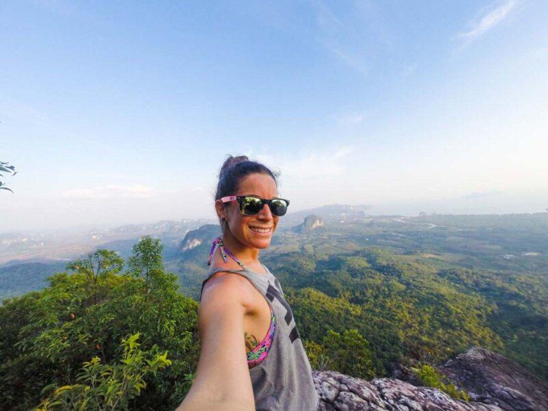 Woman hiker taking selfie with green landscape in Krabi