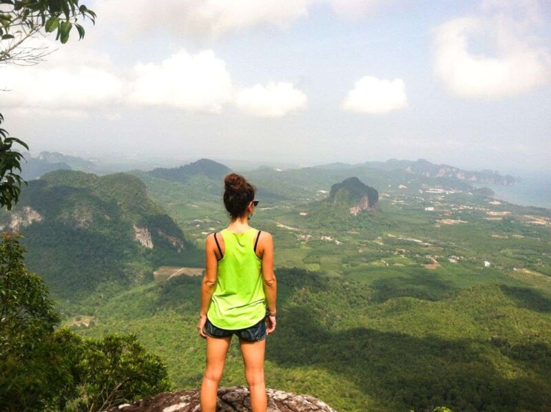 Woman looking out over rolling hills in Krabi, Thailand