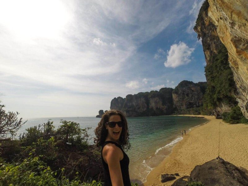Woman with beach and cliffs in the background while living in Thailand