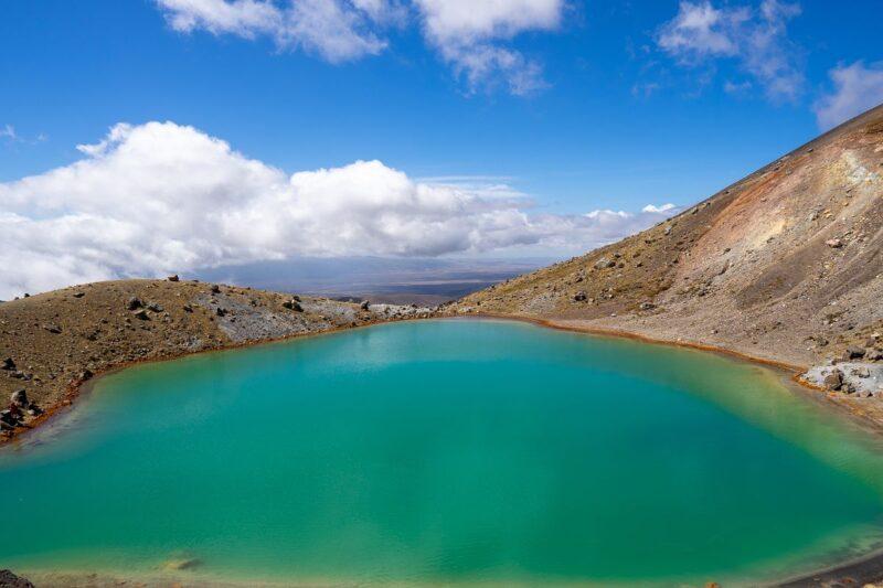 Blue Lake surrounded by arid hills on the Tongariro Hike
