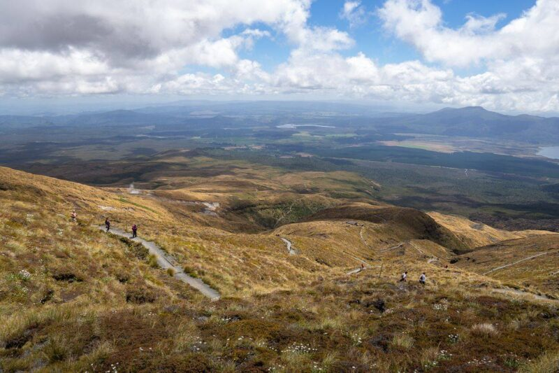 Views over Tongariro National Park with people hiking on trail in distance