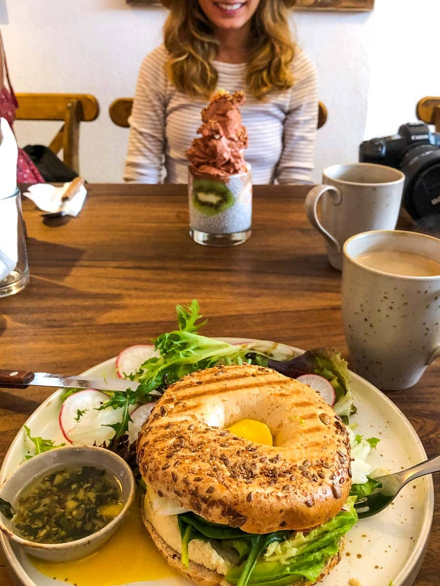 Plate with bagel sandwich and salad with person sitting across table at Anchor Restaurant in Sayulita