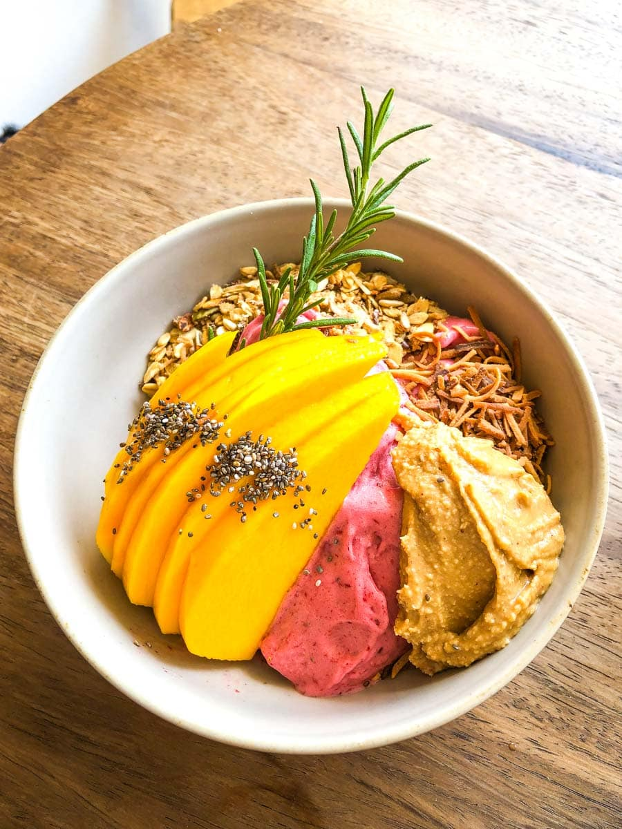 Smoothie bowl with fresh mango on top on table at Anchor - one of the best Sayulita Restaurants