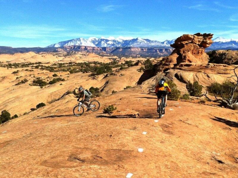 Bikers on the Slickrock Trail with snowcapped mountains in the background - one of the best things to do in Moab