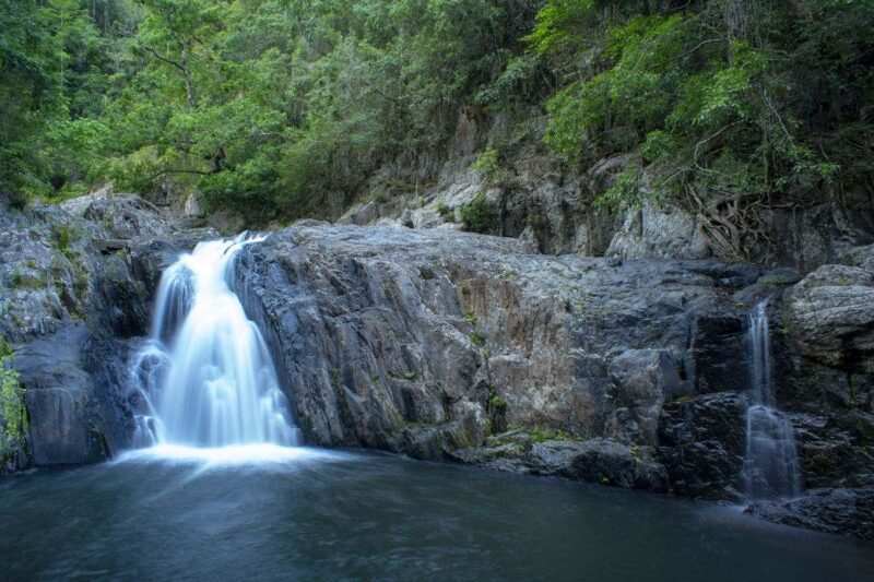 Waterfall falling over rock wall into pool at Crystal Cascades - one of the top things to do in Cairns