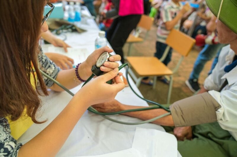 Doctor or Nurse taking someone's blood pressure - work as a doctor abroad