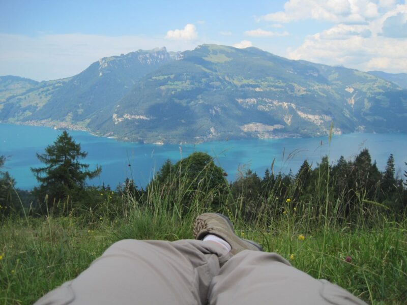 Person's legs lying on grass with view over lake and mountain in distance