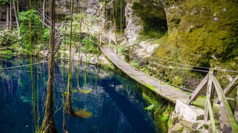 Ek Balam ruin with bridge crossing water and vines hanging down - part of your Yucatan Itinerary