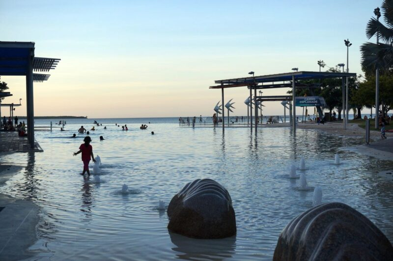 Person standing in water at Esplanade Lagoon at sunset - one of the best things to do in Cairns