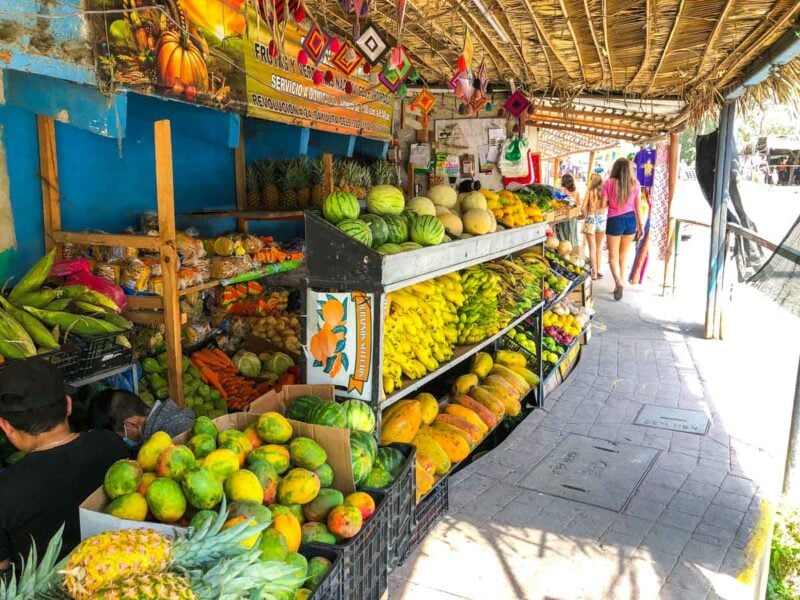 Fruit and vegetable shop on the side of the sidewalk with woman walking past in Sayulita