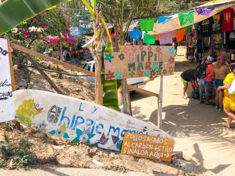 Signs stating Hippie Market in the sand with colorful prayer flags hanging in trees - visiting the market is one of the best things to do in Sayulita