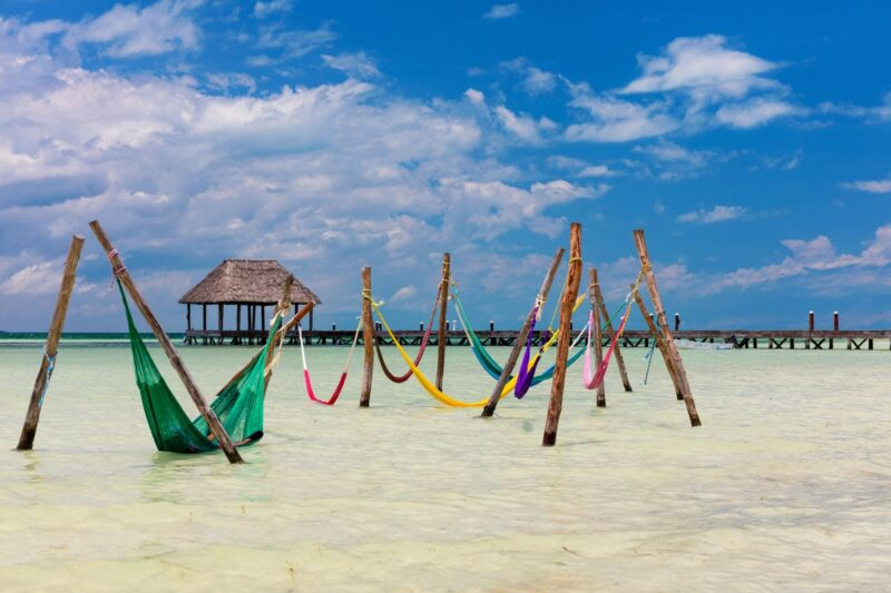 Hammocks over shallow ocean on Isla Holbox, a great addition to your Yucatan Itinerary