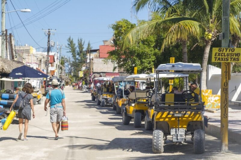 Person walking down street past beach buggies parked on the side of the road in Isla Holbox, part of any great Yucatan Itinerary