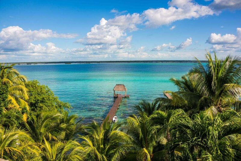 Aerial view of Lake Bacalar surrounded by palms and with jetty in water