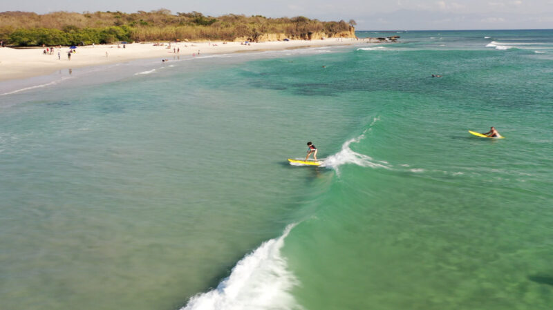 Person surfing wave with beach in background at La Lancha, one of the best Sayulita beaches