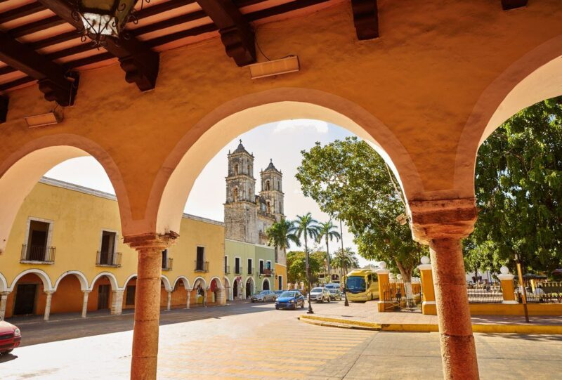 Colonial building viewed through arch in Valladolid - a must add to your Yucatan Itinerary