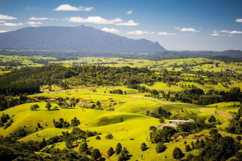 Aerial view over green fields with mountains in background at Millaa Millaa - one of the best places to visit near Cairns