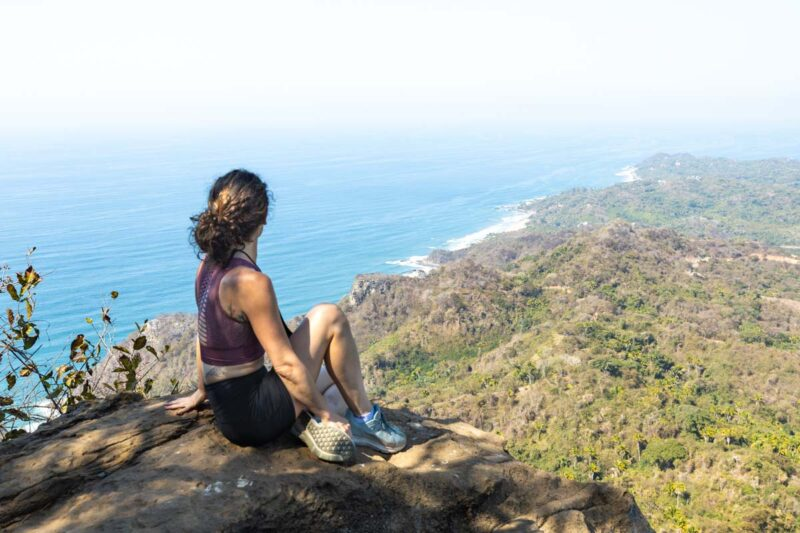 Nina sitting on rock on top of Monkey Mountain and looking out over ocean and coastline - hiking Monkey Mountain is one of the things to do in Sayulita