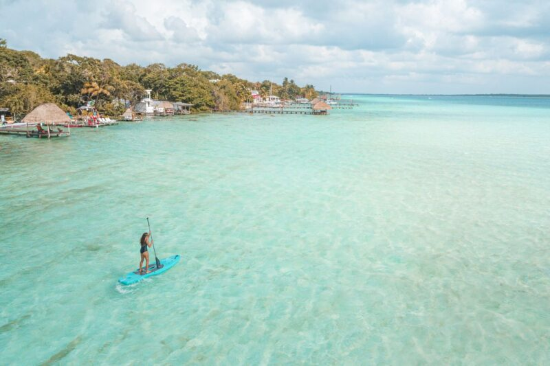 Paddleboarder in turquoise ocean with spit of land in background in Mexico