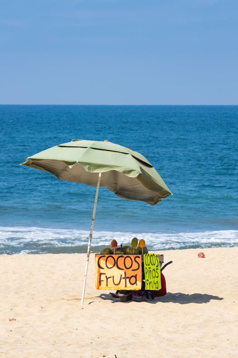 Beach umbrella and fruit stand on San Pancho beach with ocean in the background