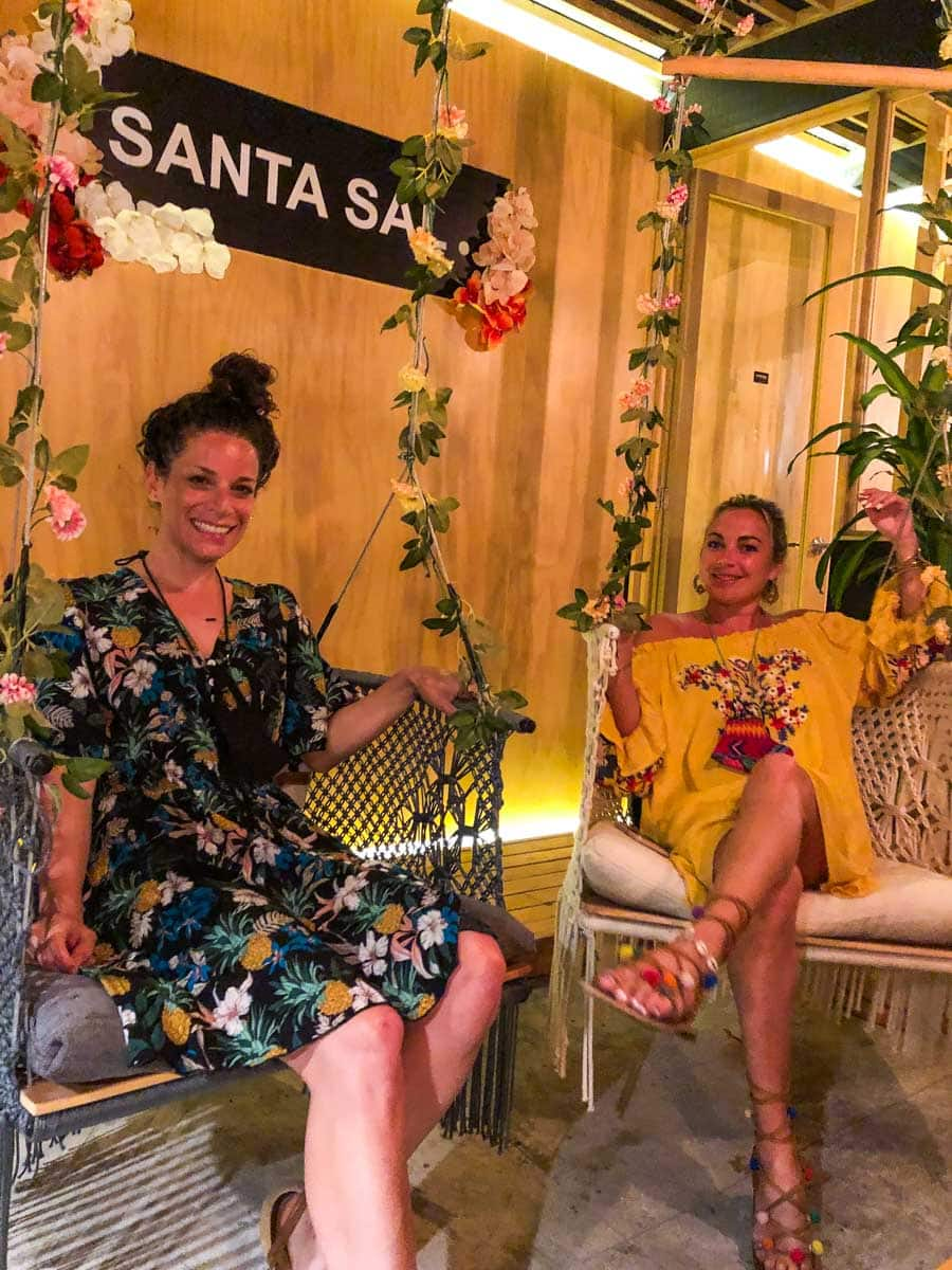 Two smiling women on swing chairs in Santa Sal - one of the best restaurants in Sayulita