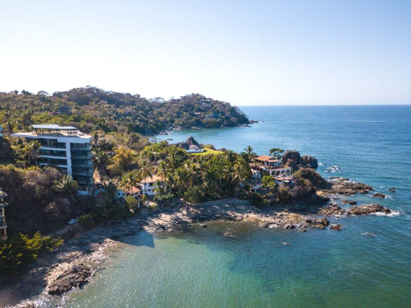 Aerial view over rocky headland, ocean and buildings in Sayulita