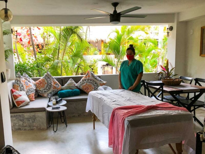 Masseuse standing by massage table in room with palms seen through window - getting a massage in your room is one of the top things to do in Sayulita