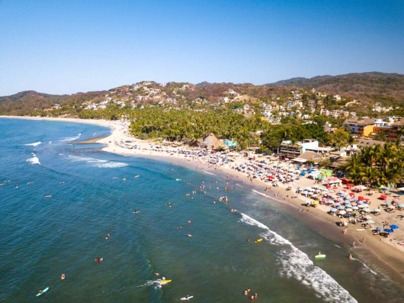 Aerial view over Sayulita beach, ocean with surfers, and buildings in background