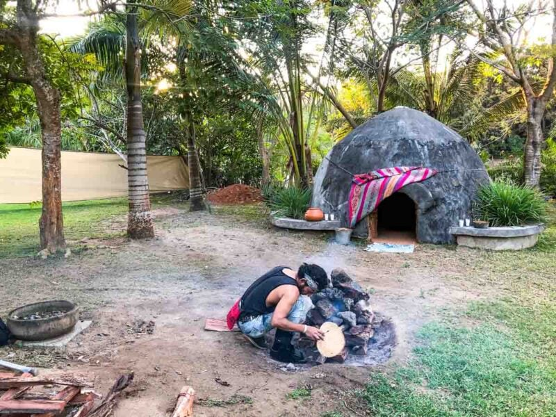 Person lighting fire outside with small rounded sweat lodge in background for Temazcal ceremony - one of the things to do in Sayulita