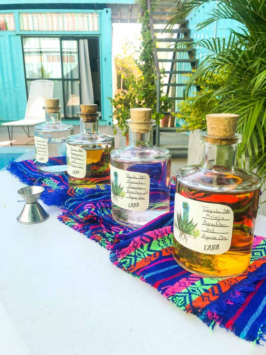Tequilas lined up on table on colorful cloths - doing a tequila tasting is one of the top things to do in Sayulita