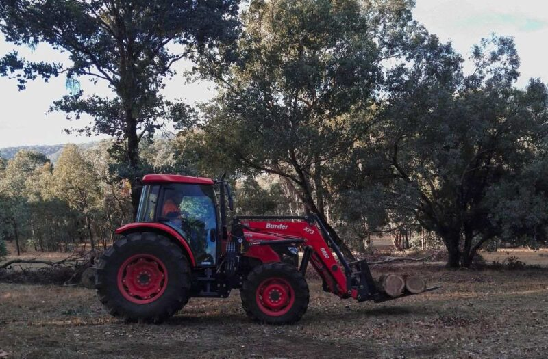 Red tractor with trees in background used for farm work in Australia