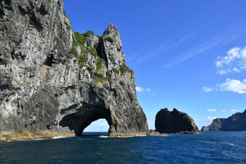 Hole in rock jutting out of the ocean in the Bay of Islands - one of the best things to do in Northland