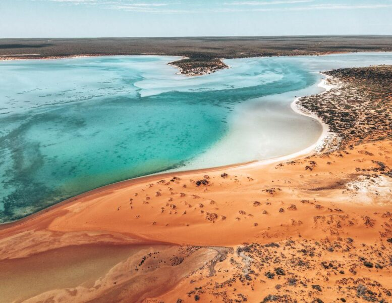 View over Big Lagoon with small island, sandy beach, and red earth