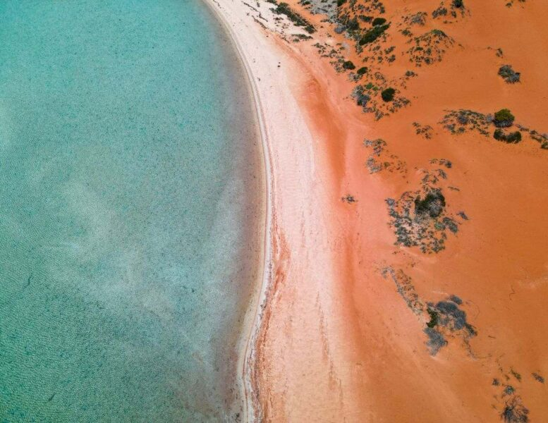 Aerial view over Big Lagoon with sandy beach and red earth - one of the best things to do on the West Coast of Australia