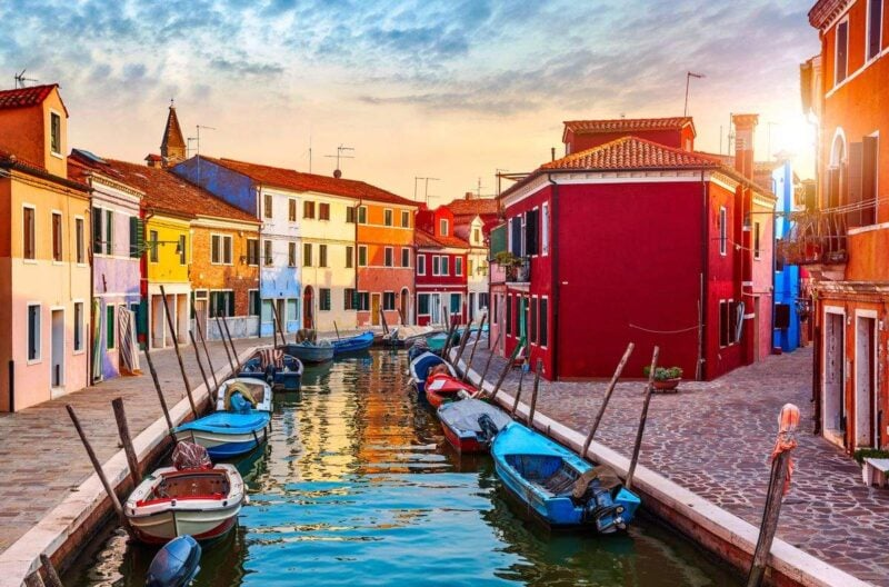Sunset over canal with boats on each side and colorful buildings on Burano - one of the best day trips from Venice