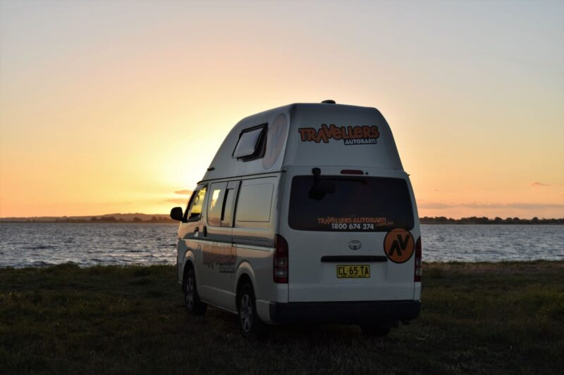 Campervan parked in front of the ocean as sunset - campervanning is one of the best things to do in Queensland