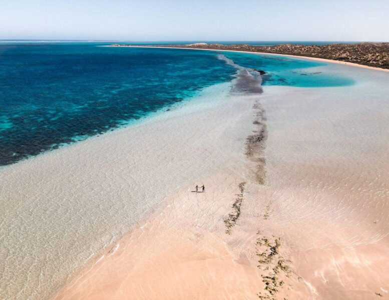 Aerial view over Coral Bay Beach with two people walking on sand in the distance - one of the best things to do on the West Coast of Australia