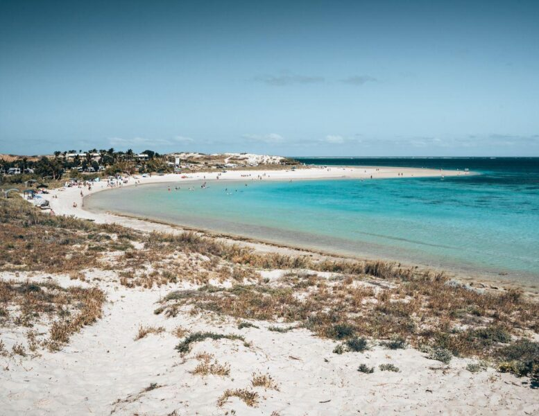 Horseshoe shaped Coral Bay Beach with turquoise water and white sand