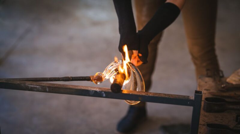 Arms and legs showing of person sculpting glass in fire at the Glass Factory in Murano - one of the best day trips from Venice