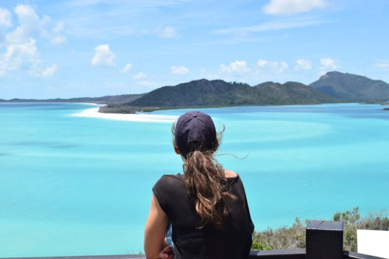Sitting woman from the back looking out at view over Whitsunday Islands and ocean - doing a Whitsundays cruise is one of the best things to do in Queensland