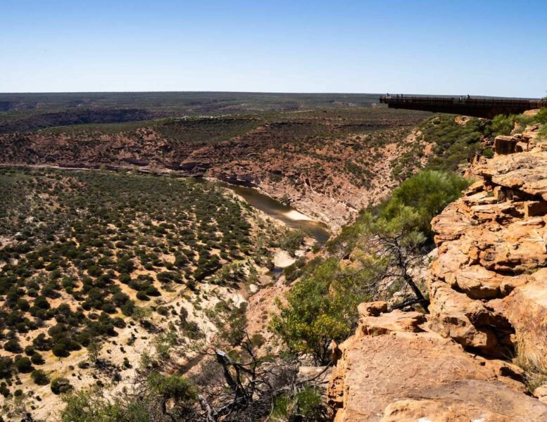 View over rocky gorge with shrub bushes and desert landscape at Kalbarri National Park