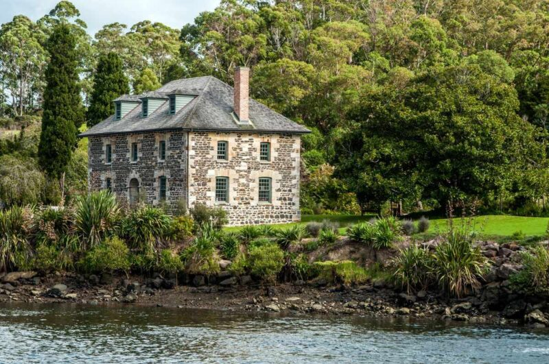 Old stone two story house on river bank with trees around it in Kerkeri, Northland