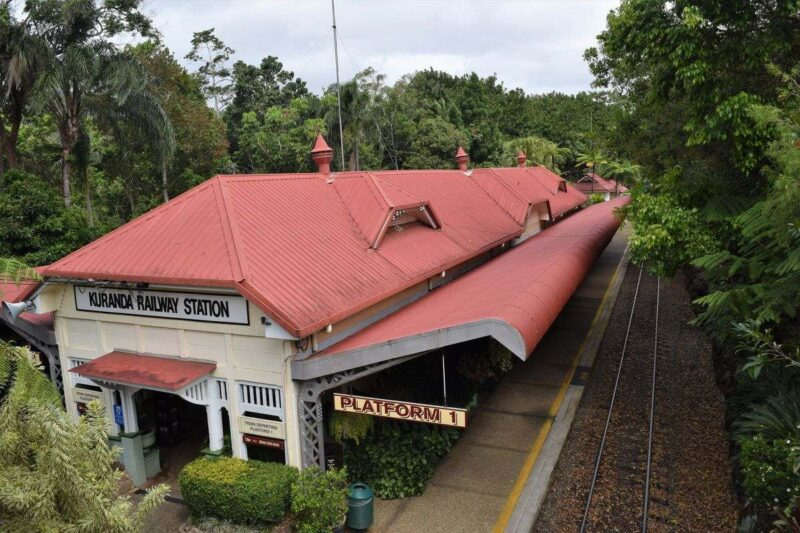 View over Kuranda train station with train tracks beside it and trees on either side - visiting Kuranda is one of the best things to do in Queensland