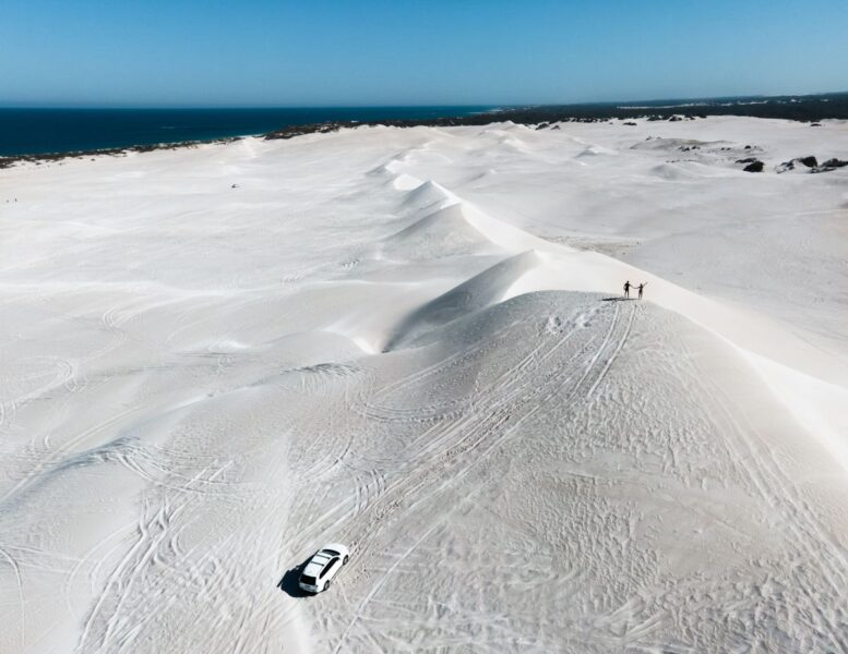 View over undulating white sand dunes with people in the distance walking on them at Lancelin
