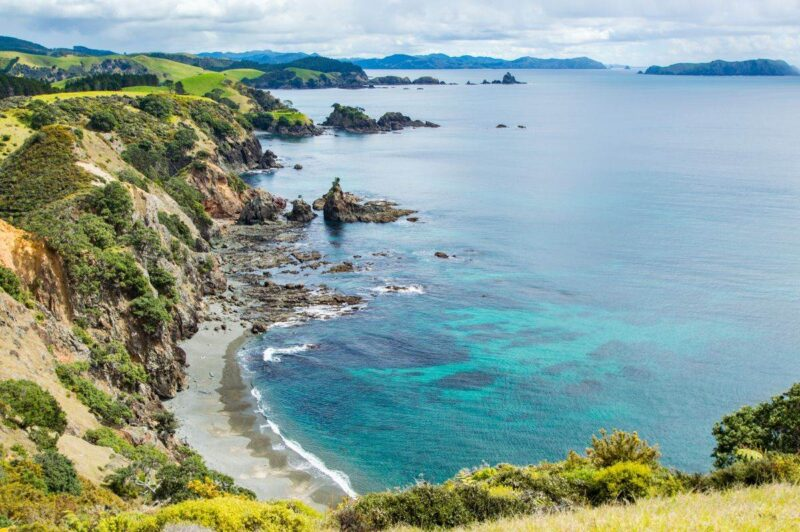 Aerial view of beach, ocean and headland at Matauri Bay - one of the best things to do in Northland